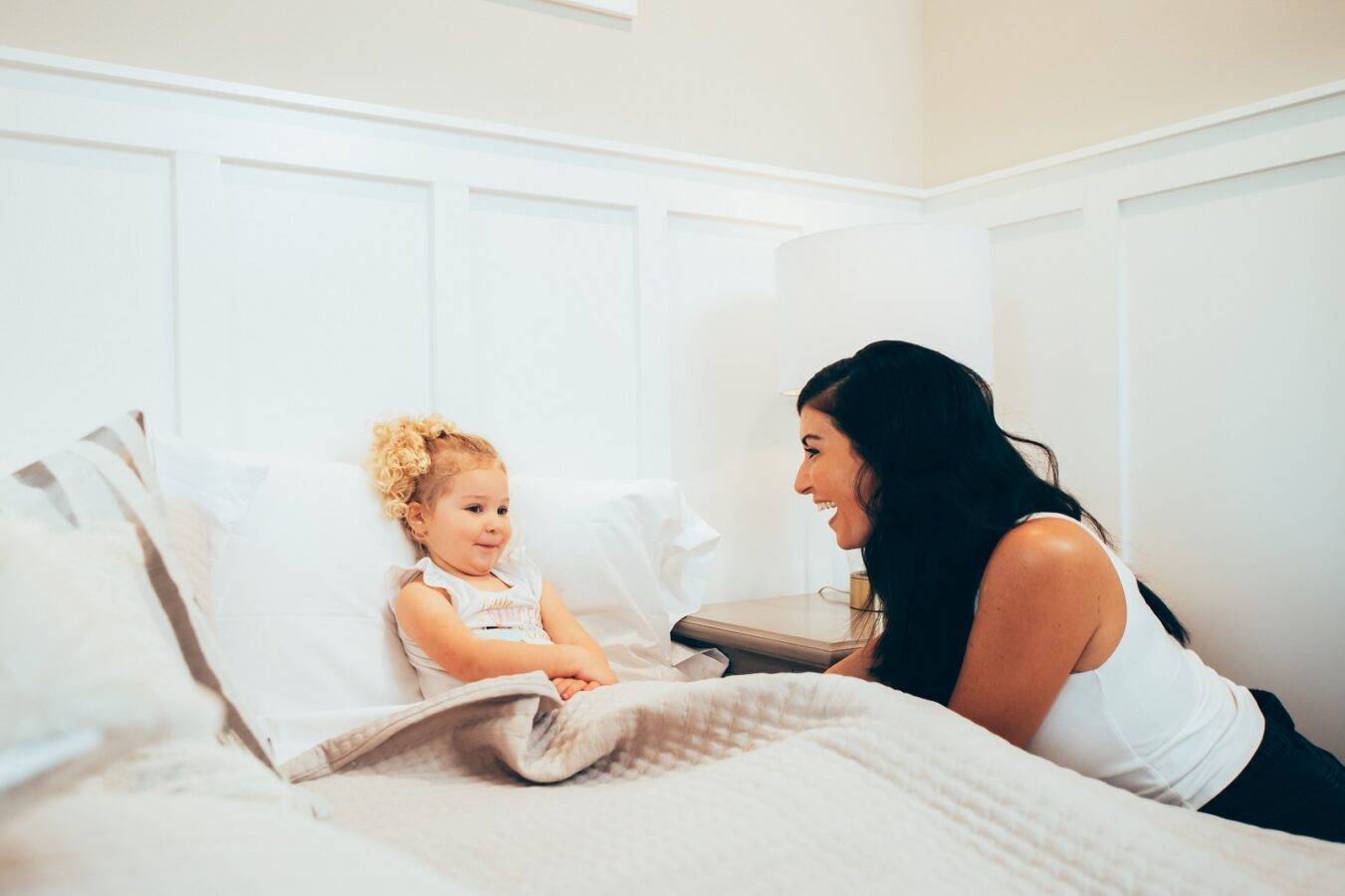 mom tucking her daughter into bed